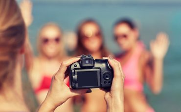 close up of smiling women photographing on beach