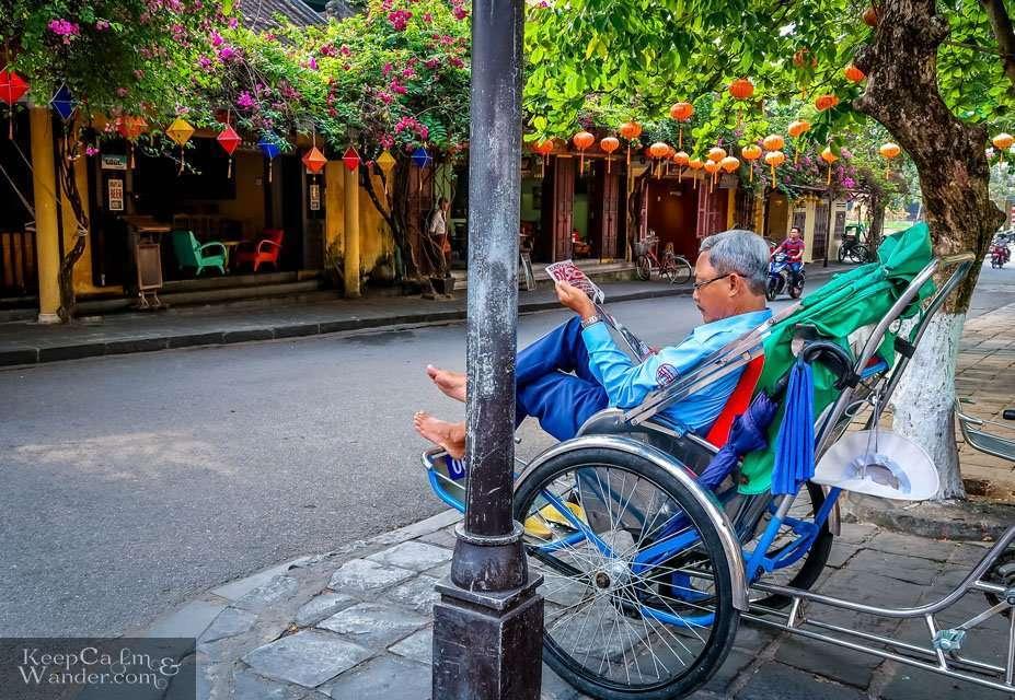 Man reading newspaper on a rickshaw